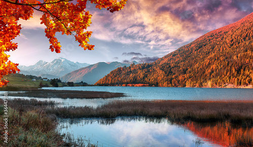 Fototapeta Incredible Nature Landscape. Colorful sky Resia Lake in Dolomites mountains, during sunrise. Scenic image of Stunning nature in Dolomites alps. Amazing Autumn Landscape. Natural background. obraz