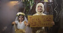 Two Girls Dressed In Halloween Mummy And Santa Muerte Costumes  With A Basket  Dancing In Old Dark Gothic Interior Asking For  Treat Showing Cardboard Label With Inscription. 4K Slow Motion 50 Fps