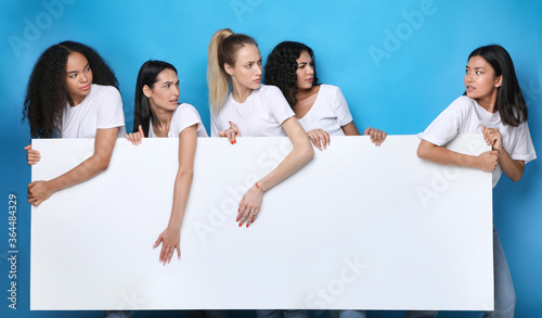 Unfriendly Girls Pulling Apart White Board Standing Over Blue Background Canvas-taulu