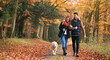 canvas print picture - Loving Couple Walking With Pet Golden Retriever Dog Along Autumn Woodland Path Through Trees