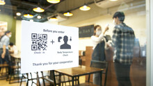 Check In And Body Temperature Check Paper Sign Measure In Front Of Restaurant With Staff Scan Body Temperature And Scan QR Code For Check In. New Normal For Protection Covid-19 After Reopening.