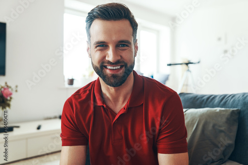 Valokuvatapetti Handsome young man in casual clothing looking at camera and smiling while spendi