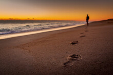 A Person Walking On The Beach Leaving Footprints In The Sand