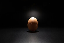 Broken Chicken Egg Shell Isolated On Black Background With Copy Space. Light Filters Through The Cracks.