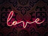 Love. Neon sign letter word Love in bright red colours glow in the dark.