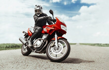 A Man Rides A Motorcycle On The Highway To The Camera. A Man On A Red Motorcycle Makes A Turn In Front Of The Camera