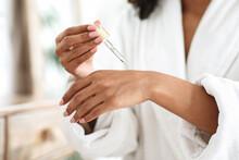 Body Care. Unrecognizable Black Woman Applying Organic Moisturising Serum On Hands Skin