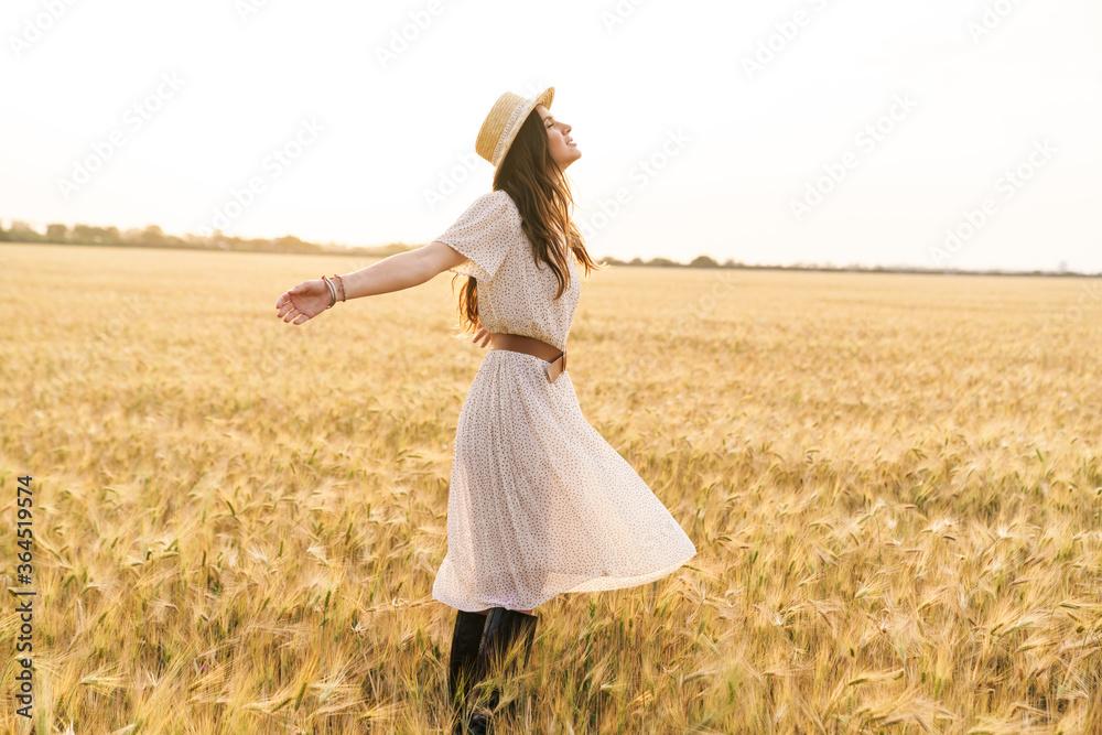 Fototapeta Photo of beautiful happy woman smiling and walking on wheat field