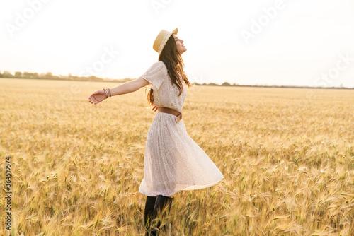 Fototapeta Photo of beautiful happy woman smiling and walking on wheat field obraz