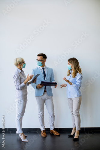 Business partners standing and looking at business results in office while wearing face masks sa an virus protection