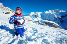 Ski Little Girl Hold Snow In Heart Shape Smiling With Mountain Summit On Background Standing On Her Knees