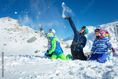 Group of kids play in snow throwing snowballs in ski outfit playing fun game tog Canvas