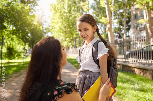 Obraz Back to school. Little girl with backpack and her mother on way to school on sunny day. - fototapety do salonu