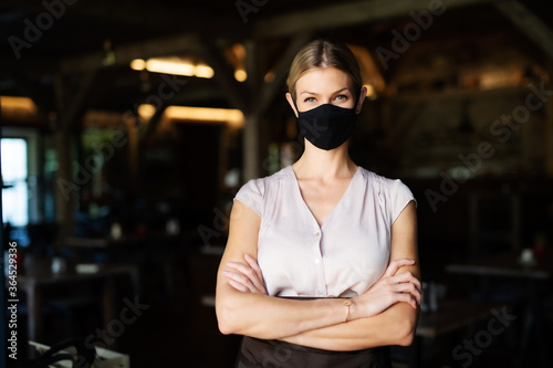 Waitress with face mask standing indoors on terrace restaurant, arms crossed.