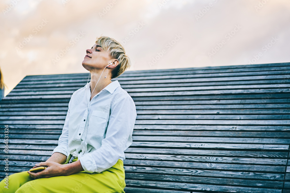 Fototapeta Young woman enjoying favourite music in earphones connected to telephone sitting on wooden bench in recreation time outdoors in urban setting.Copy space area for your advertising text message