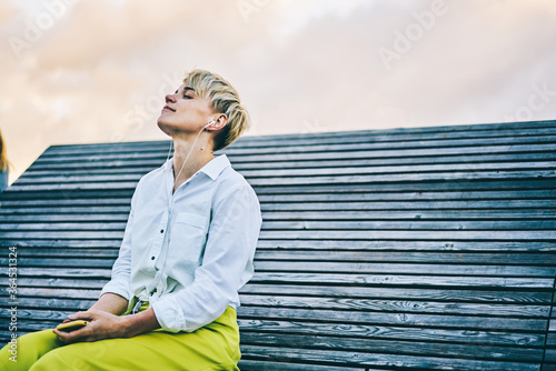 Obraz Young woman enjoying favourite music in earphones connected to telephone sitting on wooden bench in recreation time outdoors in urban setting.Copy space area for your advertising text message - fototapety do salonu