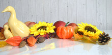 Autumn Still Life With Porcelain Ducks, Red Apples, Pumpkin, Sunflowers, Maple Leaves, Cape Gooseberries As Concept For Halloween Or Thanksgiving Day Decorations.