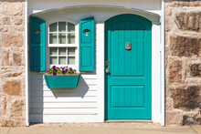 Partial Front Exterior Of White Cottage With Teal Shutters And Door And Teal Window Box With Purple Petunias
