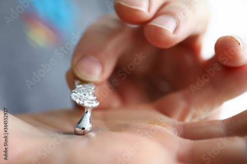Fotografie, Obraz Male hand holding piece of liquid gallium