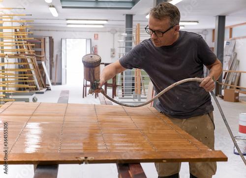 Craftsman applying varnish to wood jalousie using airbrush in carpentry workshop - 364555305