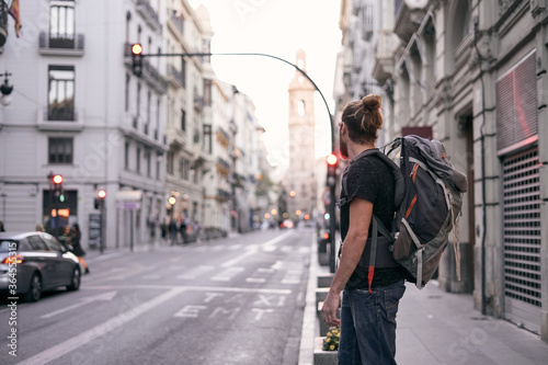 Handsome traveling man with backpack and in casual wear standing on street during city stroll - 364555315