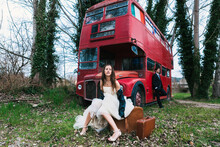 Bride In Wedding Dress And Leather Jacket Sitting On Retro Suitcase And Groom In Suit Leaning On Red Double Decker Bus Abandoned In Forest