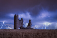 Low Angle Dramatic Scenery With Aged Destroyed Stone Fortress Located On Grassy Terrain Against Dark Cloudy Sky With Various Lightnings In Evening