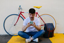 Man Checking His Smartphone. He Is Sitting On The Floor With A Bike And A Backpack.