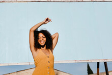 Low Angle Of Happy African American Female In Brown Summer Dress Smiling At Camera While Standing With Arms Raised On Street Against Blank Billboard In Sunlight