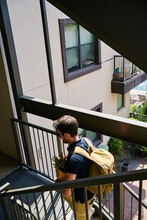 From Above Back View Of Male With Paper Bags And Backpack Walking Upstairs In Modern Building