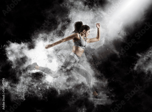 Sporty young woman running on smoke background Fototapeta
