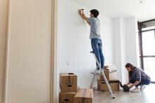 Young Man Standing On Ladder H...