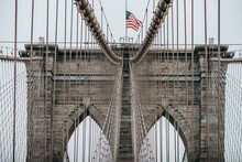 Low Angle Of Stone Towers With Pointed Arches Of Suspension Brooklyn Bridge With American Flag On Cloudy Day