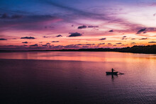 Silhouette Of Person Rowing On...