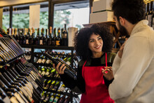 Charming Curly Girl In Red Apron Advising Wine Sorts To Man Working In Wine House Market.