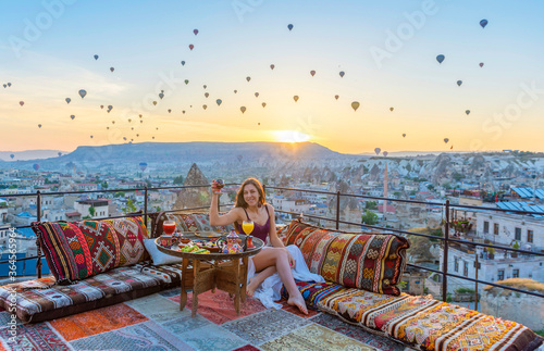 Foto A woman have breakfast on one of the Cappadocia roof in early morning sunrise, when balloons fly