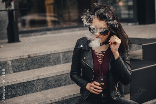 Beautiful stylish brunette smoking an e-cigarette in public places Wallpaper Mural