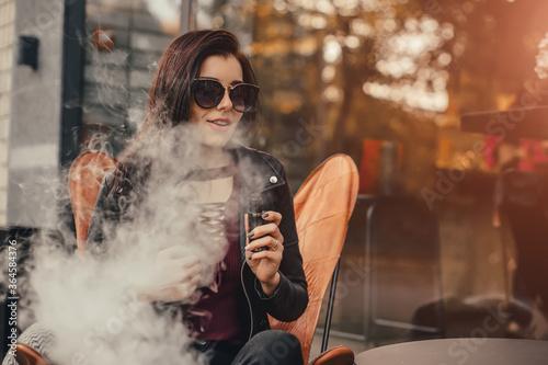 Beautiful stylish brunette smoking an e-cigarette in public places Canvas Print