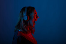 Photo Of Young Woman Listening Music At Headphones With Neon Lights And Screaming