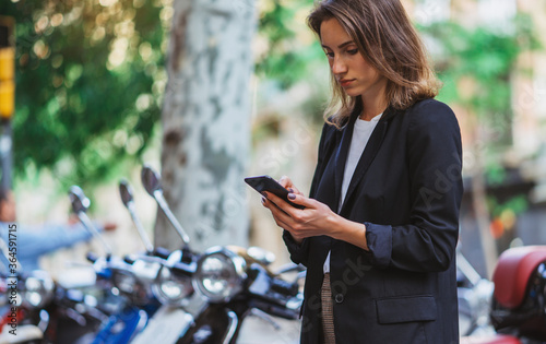 serious girl in a black jacket uses app in smartphone to rent and pay moped to t Canvas-taulu