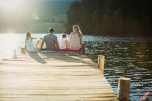 Family Sitting At The Edge Of Dock Over Lake