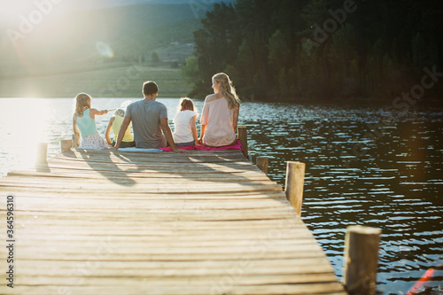 Cuadros en Lienzo Family sitting at the edge of dock over lake