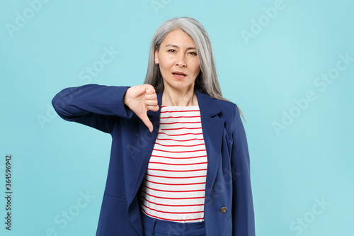Displeased gray-haired business woman in blue suit posing isolated on pastel blue wall background studio portrait Canvas Print