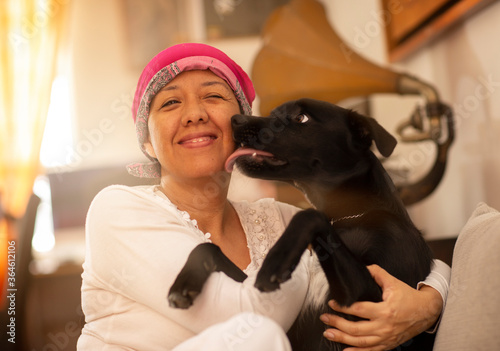 Valokuva latin woman hugging her pet, woman with pink scarf on her head due to breast can