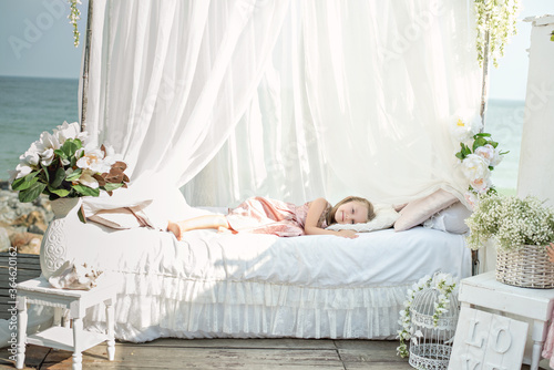 Valokuva Close up portrait blonde girl with long hair in a beautiful pink powdery dress sleep in a white bed with chiffon canopies, decorated with wisteria, flowers against the background of the sea