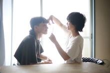 男性の髪を切る女性