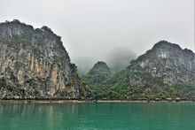 Islands In Halong Bay In The Fog. Calm Emerald Water And A Narrow Strip Of Sand On The Shore. Bizarre Rocky Islands Hide In A Foggy Haze. UNESCO Heritage. Vietnam.