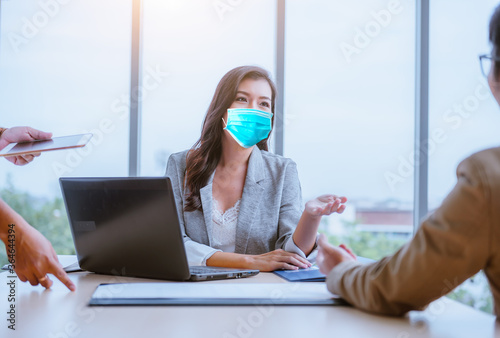 Fotografie, Obraz Businesswoman and partner business team work meeting are discussing with new strategy business project with laptop and file document at office,she wearing face mask to protect  virus