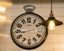 """Hanging On The White Wall Vintage Classic Clock And Copper Lamp In A French Coffee Shop. Inscription On The Watch """"Paris"""""""