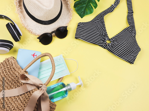 Obraz COVID-19 prevention , summer and new normal concept, top view of   bikini swim wear  and women's vacation accessories with medical mask and sanitizer gel  in woven bag on yellow background. - fototapety do salonu